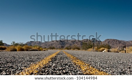 This road leads towards mountains in the desert