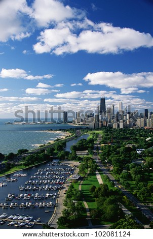 This shows Lincoln Park, Diversey Harbor, and Lake Michigan looking south toward the skyline. It has morning light in summertime. There are boats moored in the harbor next to the lake.