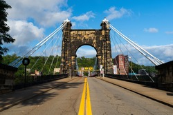 This shows the approach roadway and masonry tower of the historic Wheeling Suspension Bridge that carries the National Road over the Ohio River in Wheeling, West Virginia.