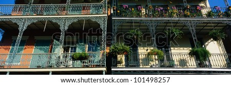 This shows two buildings in the historic French Quarter on Bourbon Street. The buildings have lattice work railings with potted flowers decorating the balconies.