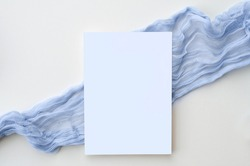 This simple and elegant hand styled photograph features a 5x7 vertical card set on top of a dusty blue gauzy table runner. Perfect for featuring wedding invitations, baby shower invitations, save the