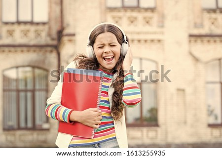This song is a celebration of the joy. Happy little girl singing along to her favorite song. Small child enjoys school song playing in headphones. New song and new emotions.