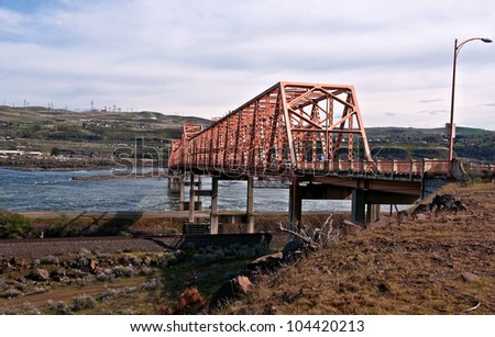 This stock image is a landscape of The Dalles bridge taken from the Washington side of the Columbia river.  This steel cantilever bridge connects Wa. state and Oregon.