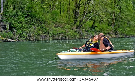 This sweet photo of romance shows a young Caucasian couple giving a kiss while on a mountain river kayaking.