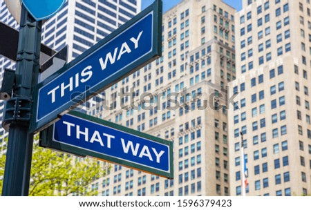 This way, that way crossroads street sign, blue color road sign, This and that alternative choice concept. Highrise buildings background,