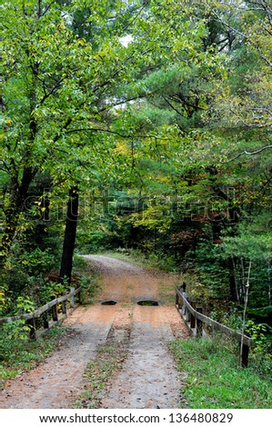 This winding New England road crosses a small stream via a bridge.  It is early fall, with the foliage just beginning to turn, and a light rain has left puddles in the road.