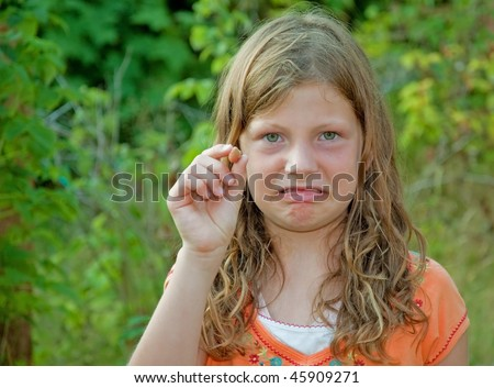 This 8 year old Caucasian girl is making a scowling facial expression over having just picked a rotton raspberry.