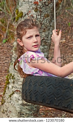 This 9 year old Caucasian girl is swinging in a tire swing.  She has a serious expression on her face.  She has long brown hair as she is playing outside.