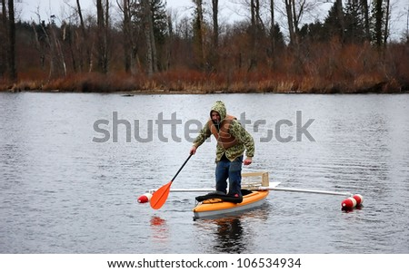 This young man is standing in a canoe that has outriggers on it, trying to tip it over.  He's wearing a lifevest, and camoflauge sweatshirt in cold weather.