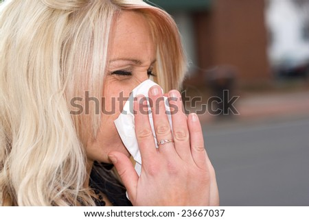 This young woman sneezing into a tissue either has a cold or really bad allergies.