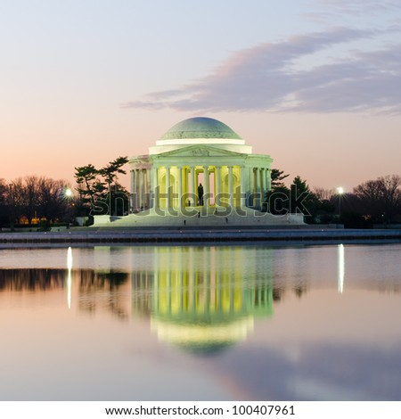 Thomas Jefferson Memorial silhouette at sunrise with mirror reflection on water, Washington DC United States