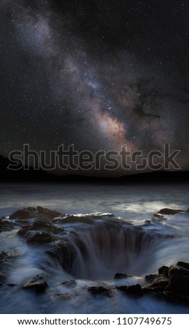Thor's well under milky way with mountains in the background. Long exposure with silky water floating into the hole.