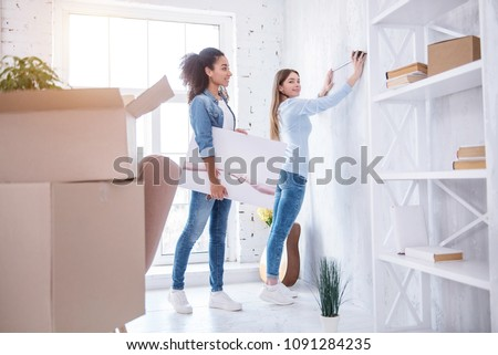 Thorough measurement. Upbeat slender girl measuring the wall, wanting to hang a picture, while her charming roommate holding it