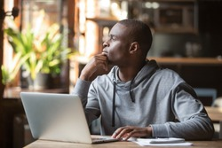 Thoughtful african american businessman lost in thoughts search for inspiration sit at cafe table using laptop, dreamy pensive contemplative black student looking away thinking of new creative ideas