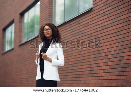 Thoughtful. African-american businesswoman in office attire smiling, looks confident and serious, busy. Finance, business, equality and human rights concept. Beautiful young model, successful. Stock photo ©