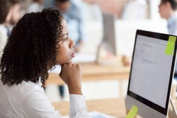 Thoughtful African American female employee busy at computer writing business email to partner, distracted from work dreaming or thinking, concerned black woman worker considering problem solution