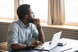 Thoughtful african American male employee in glasses sit at desk distracted from computer work pondering, pensive biracial man look in distance thinking or planning, business vision concept
