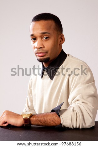 Thoughtful African American man resting his arm on a table and looking at the camera