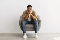 Thoughtful African American Man Thinking Sitting In Chair Over Gray Wall Background Indoors. Full-Length Shot Of Pensive Millennial Guy Reflecting On Problems, Front View