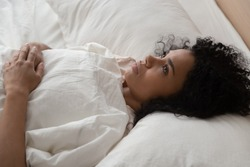 Thoughtful african American millennial girl lying in white comfortable bed lost in thoughts think of problem solution, pensive black woman relaxing in bedroom suffer from insomnia sleep deprivation