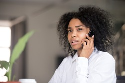 Thoughtful African American woman talk over phone looking in distance considering idea, pensive black female have cell conversation thinking of problem solution, being serious making decision