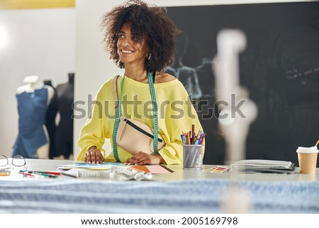 Thoughtful African-American woman with tape measure aat table at sewing class Stok fotoğraf ©