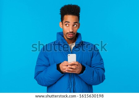 Thoughtful and creative cute african american guy thinking, use imagination to write cute message girlfriend, inviting come date valentins day, holding smartphone pensive, blue background