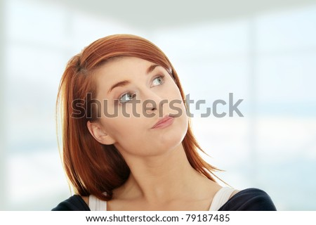 Thoughtful and worried woman looking up - stock photo