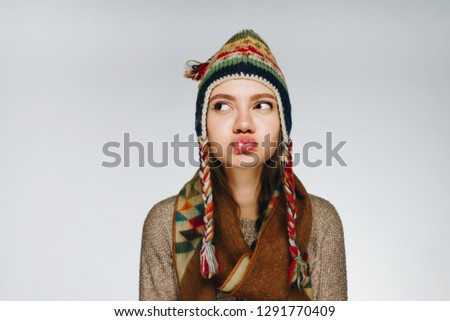 thoughtful annoyed girl in a hat with Norwegian patterns pouted her lips with a duck and looks up