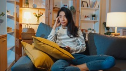 Thoughtful Asia lady holding phone feeling sad waiting for call sit at sofa in living room at house night feel lonely, Sad depressed teenager spend time alone, Social distance, Coronavirus quarantine.