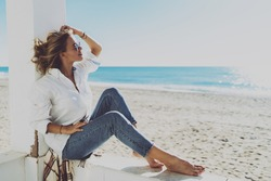 Thoughtful attractive woman dressed in stylish casual clothes enjoying good sunny weather on a sunny beach. Gorgeous model look blonde female in sunglasses relaxing on a warm windy day on a beachside.