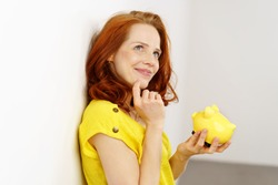 Thoughtful attractive young redhead woman leaning back against a wall deciding how to spend her savings from her handheld yellow piggy bank