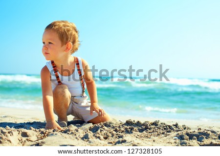 thoughtful baby boy sitting on the beach