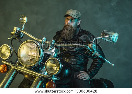Thoughtful Bearded Biker Man in Black Leather Jacket with Cap Sitting on his Elegant Motorcycle and Looking Into the Distance Against Smoky Wall Background.