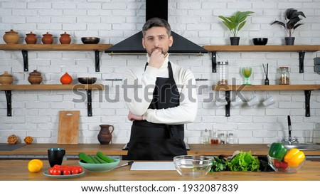 Thoughtful bearded man chef cook teacher in black apron looking camera listen online student housewife question, records remote video culinary webinar master class course lesson in home modern kitchen Stock photo ©