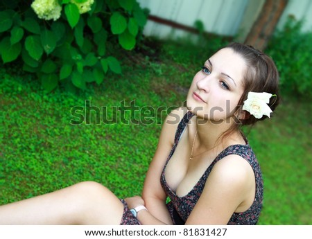 Thoughtful beautiful girl sitting on green grass and looking