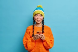 Thoughtful beautiful teenage girl holds mobile phone and sends text messages thinks what answer to give reads comments under her post in social networks dressed in winter clothes isolated on blue wall