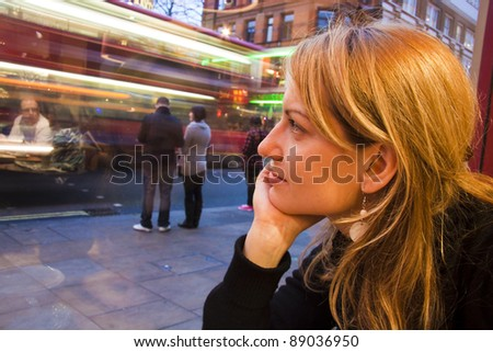 Thoughtful beautiful young lady looking at the street through the cafeteria window.. Blurs of London's traditional bus driving by and some reflexions from the interior can be seen in the glass
