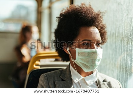 Thoughtful black businesswoman wearing face mask for virus protection and looking through the window while traveling by public transportation.