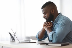 Thoughtful Black Writer Working With Laptop At Home Office. African American Freelancer Man Sitting At Desk And Looking At Computer Screen With Pensive Face Expression, Side View With Copy Space