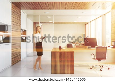 Thoughtful blonde businesswoman standing in stylish office with white and wooden walls, tiled floor, white and wooden computer desk and bookcases with folders. Toned image #1465446635