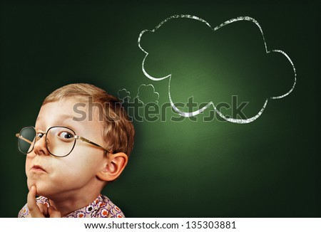 Thoughtful boy funny portrait with abstract idea clouds on chalkboard