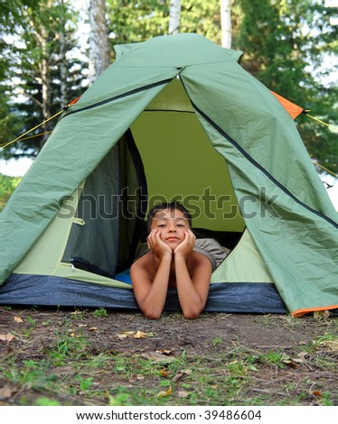 thoughtful boy in camping tent summer forest