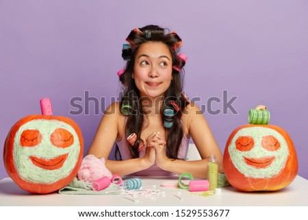 Thoughtful brunette Asian woman keeps hands pressed together, thinks what to wear for date, wears curlers on long dark hair, poses at white table, going to apply makeup, two funny pumpkins drawn faces