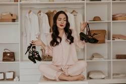 Thoughtful brunette woman in pink pajamas looks at sandals. Lady with red lips poses in dressing room and choose between two pairs of high heels.