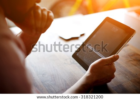 Thoughtful business man looking to the digital tablet screen while sitting in modern loft interior at wooden table,entrepreneur or freelancer work on touchscreen pad at the office,flare sun and filter