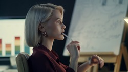 Thoughtful business woman analyzing income charts on computer in night office. Pensive woman working late with financial reports in dark office. Closeup woman having overtime work in evening office