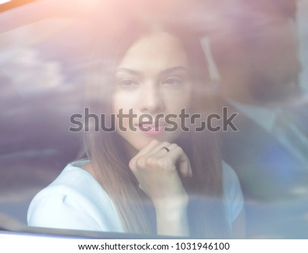 thoughtful business woman sitting in car backseat