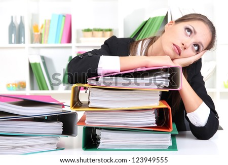 thoughtful business woman with documents in her workplace