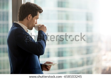 Thoughtful businessman drinking coffee, looking through window at big modern city, having break, deep in thoughts, enjoying view, waiting for meeting to start, making business decision, copy space